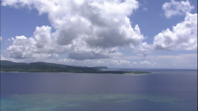 Fluffy clouds float in the sky over Iriomote Island and the East China Sea near Okinawa, Japan.