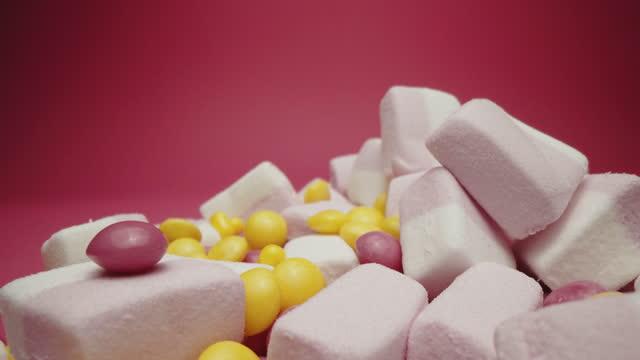 ふわふわマシュマロとカラフルなサワーキャンディー - ジェリービーンズ点の映像素材/bロール
