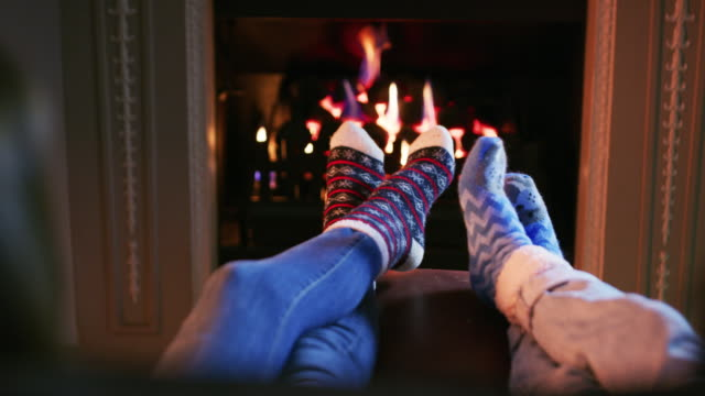 fluffy socks and a fireplace, life's perfect - piedi alzati video stock e b–roll