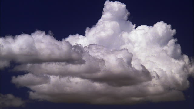 Fluffy white cloud billowing in blue sky, Maui Available in HD.