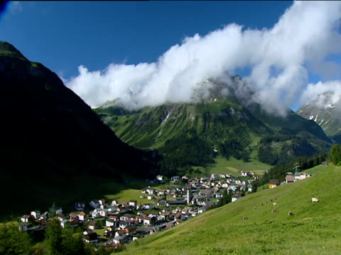 Fluffy white clouds above mountain peak village clustered in valley below Austria