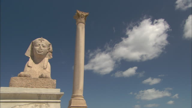 Fluffy white clouds drift over a Sphinx and a solitary column in Cairo.