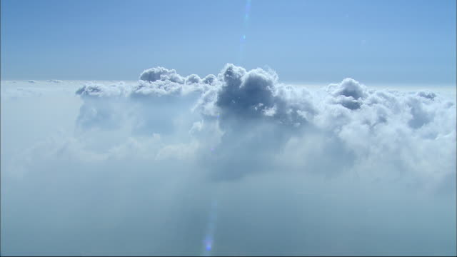 fluffy white clouds float above mist in a blue sky. - 2009 stock videos & royalty-free footage