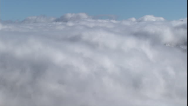 Fluffy white clouds float in a blue sky.