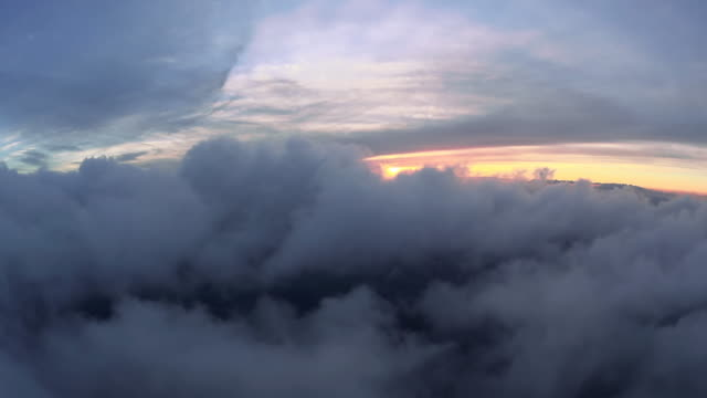 WS AERIAL POV Fluffy white clouds in sky at sunset