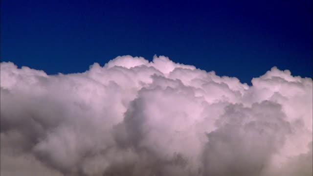Fluffy white cumulus clouds roll across blue sky, Maui Available in HD.