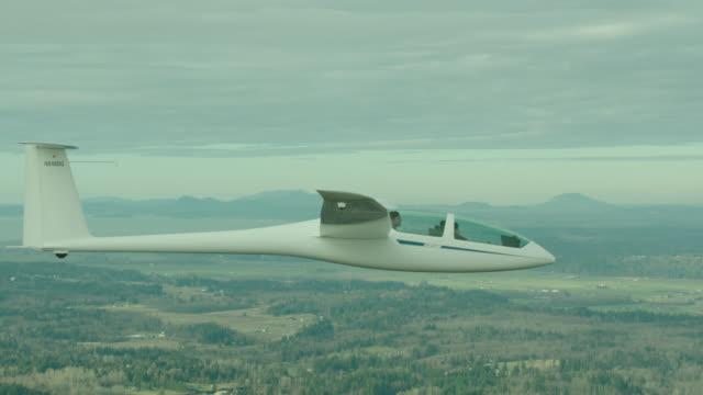 a-a dg flugzeugbau dg-1000 glider flying over rural countryside - segelflugzeug stock-videos und b-roll-filmmaterial