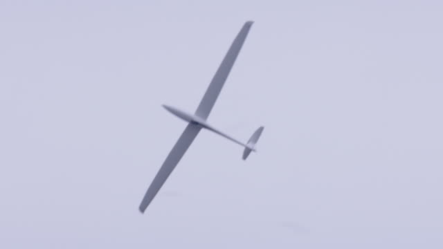 g-a dg flugzeugbau dg-1000 glider towed behind piper pa-25-235 single engine private plane t/o on rural open field, camera follows in flight to landing - segelflugzeug stock-videos und b-roll-filmmaterial
