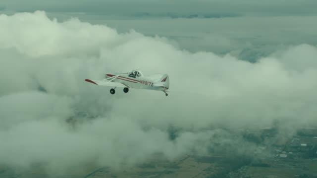 vidéos et rushes de a-a dg flugzeugbau dg-1000 glider towed behind piper pa-25-235 single engine private plane over clouds/rural countryside - transport aérien