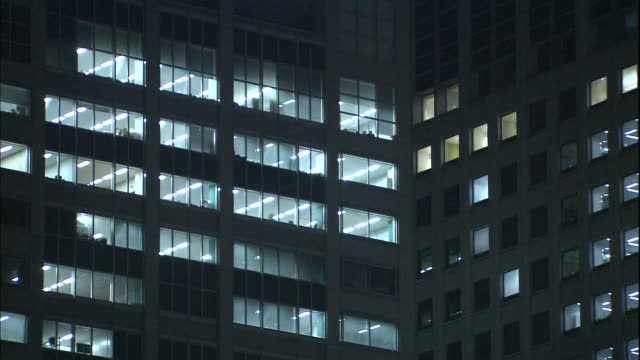 fluorescent ceiling lights illuminate office windows in a skyscraper. - 建物の正面点の映像素材/bロール