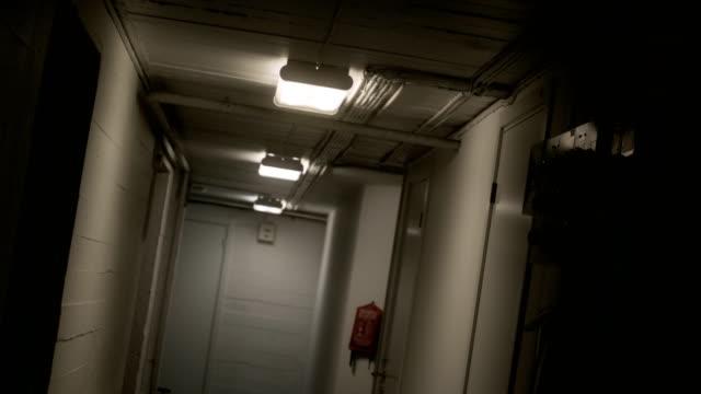 fluorescent light flicker on in a creepy hallway - korridor stock-videos und b-roll-filmmaterial