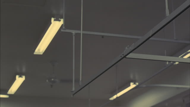 fluorescent lights hang from a ceiling. - fluorescent light stock videos and b-roll footage