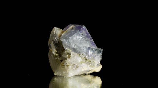 vidéos et rushes de cristaux de fluorine tournant sur fond noir - pierre précieuse