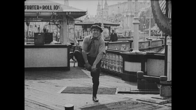 1917 flustered man (buster keaton) drops mallet on startled fair worker's foot - 1917 stock videos & royalty-free footage