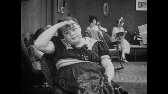 1917 Flustered man (Fatty Arbuckle) in drag gets overheated when he sees woman fixing her stocking / man in drag removes hat and wig