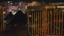 Fly by Mandalay Bay hotel and casino revealing Las Vegas Strip at night.
