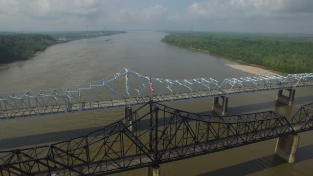 fly down to american flag on bridge - Drone Aerial 4K Mississippi river bridge and barge 1of14, everglades, gulf delta, new orleans, st louis, with cruise boats sailing and wildlife 4K Transportation