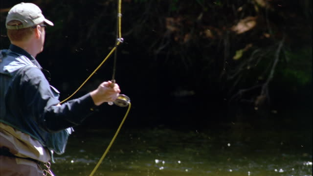 SLO MO MS PAN Fly fisherman casting fishing line in Grand Lake Stream / Maine, USA