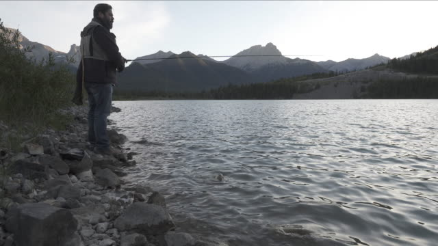 Fly fisherman casts line into mountain lake, dawn