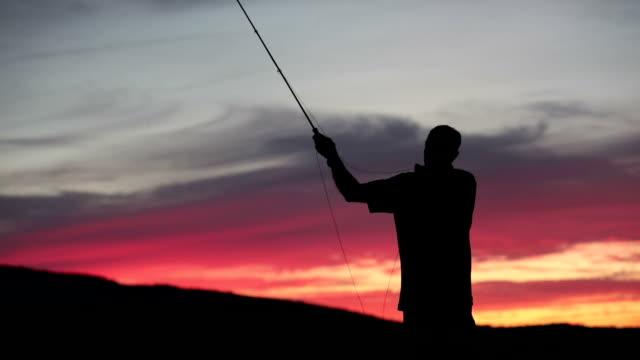 Silhouet van de visser op Lake vliegvissen bij zonsondergang