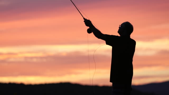 fly fishing fisherman silhouette on lake at sunset - fly fishing stock videos and b-roll footage