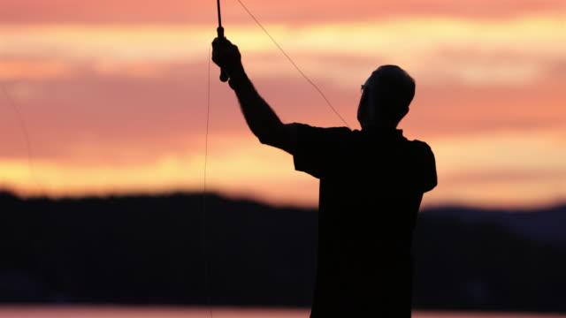 Fliegenfischen Sie, Silhouette der Fischer auf See bei Sonnenuntergang