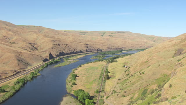 MS AERIAL Fly over Clearwater River with train tracks / Spalding, Idaho, United States