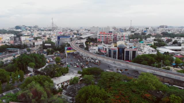 賑やかな南インドの都市でラッシュアワーで交差点を持つ地下鉄の列車や道路の上を飛ぶ - インド点の映像素材/bロール