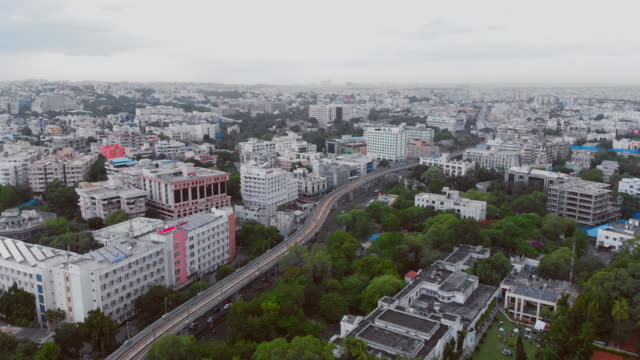 fly over metro trains and roads with intersections at rush hour in bustling south indian city - development stock videos & royalty-free footage
