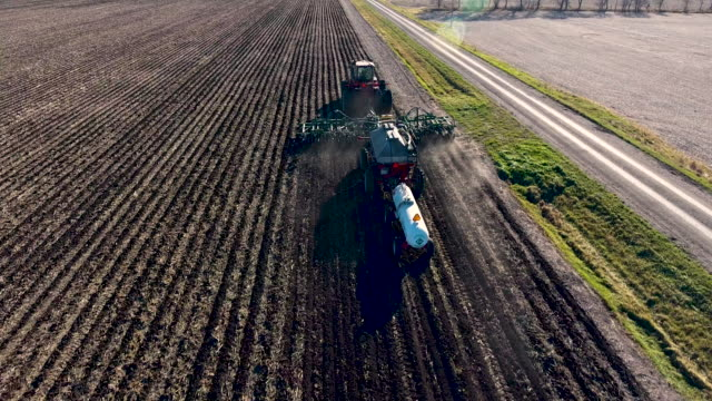 fly over of a tractor planter planting - macchina agricola video stock e b–roll