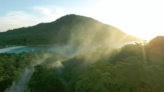 vídeos de stock, filmes e b-roll de fly through smoke to reveal a paradise bay in ko racha island thailand - david ewing
