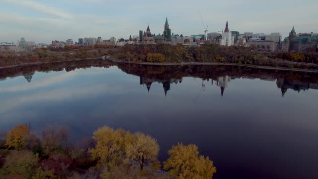 vídeos de stock, filmes e b-roll de fly through steam over ottawa river to canadian parliament - ottawa