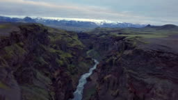 Fly up from dark volcanic canyon in Icelandic mountains