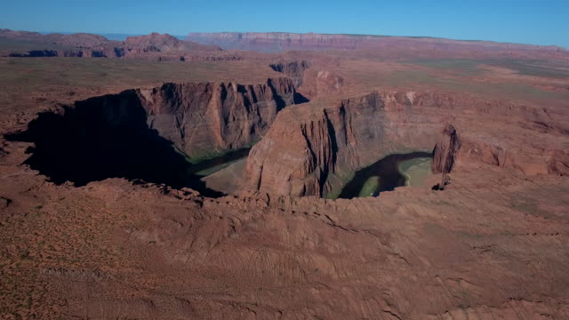 epic long fly up to horse shoe bend 4k, drone aerial view of horseshoe bend along the colorado river leading to grand canyon and glen canyon. morning and evening light with sun on the horizon - grand canyon national park stock videos & royalty-free footage