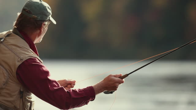ms pan fly-fisherman casting fishing line in river / the forks, maine, usa - fishing rod stock videos & royalty-free footage