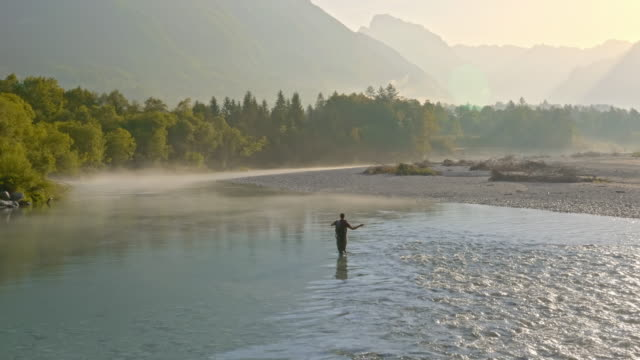 AERIAL Fly-fishing on the misty river in the morning sun