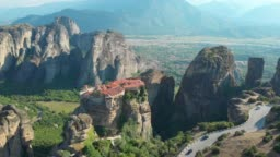 AERIAL: Flying above a scenic asphalt road leading past an old Greek monastery.