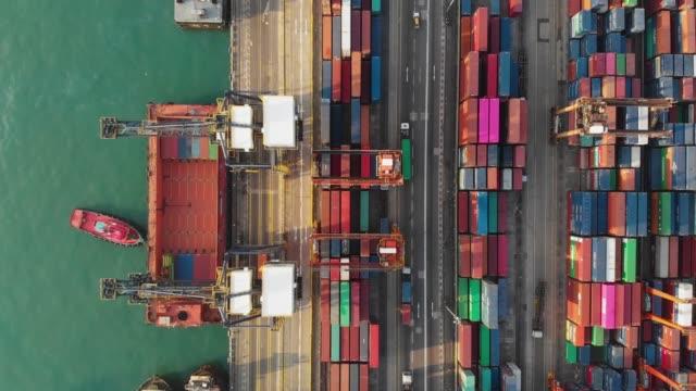 fliegen oben und dolly weiterleiten von containerschiff im industriehafen. - box container stock-videos und b-roll-filmmaterial