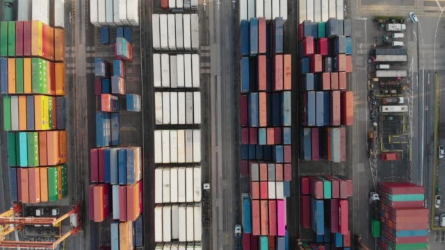 flying above and zoom out of container ship in industrial port. - container stock videos & royalty-free footage