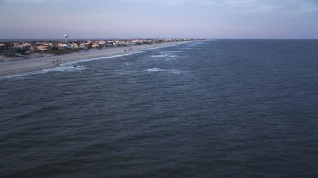 vídeos y material grabado en eventos de stock de flying above open water along shoreline of long beach island, new jersey at dusk. shot in november 2011. - artbeats