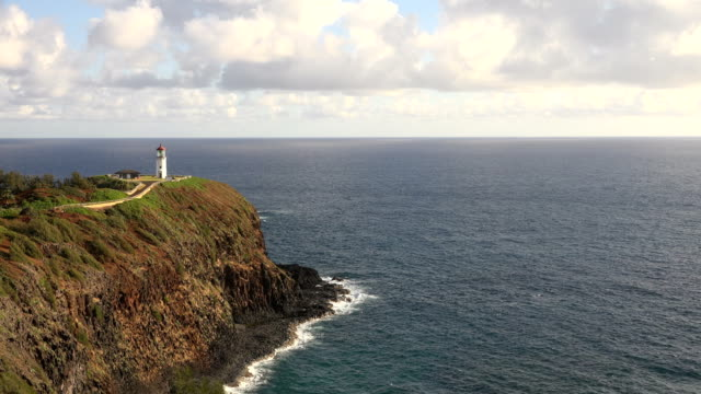 flying above rocky coastline and lighthouse on kauai island - butte rocky outcrop stock videos & royalty-free footage