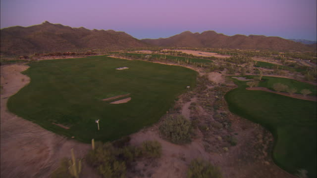 POV Flying above saguaro cactus covered desert and landing at golf course at sunset, Tucson, Arizona, USA