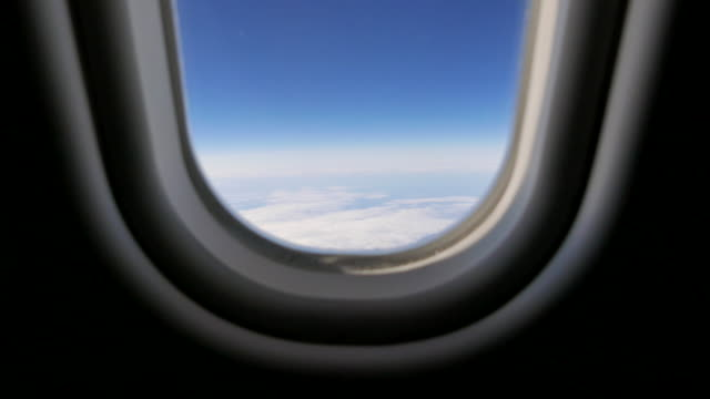 flying above the clouds. airplane window view. high in the sky background - closing stock videos & royalty-free footage