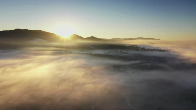 flying above the clouds and mountain in sunrise time - land stock videos & royalty-free footage