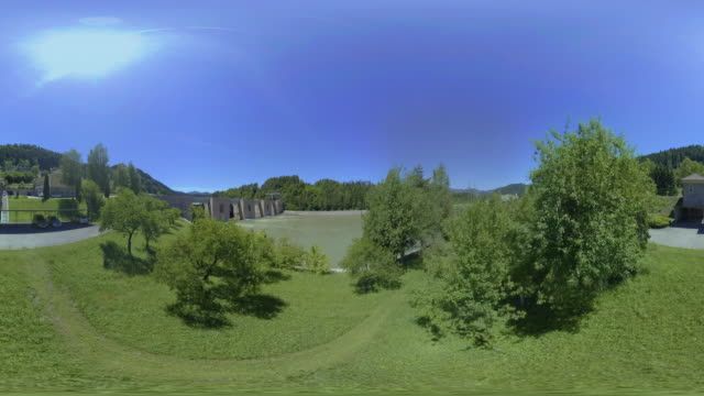 AERIAL VR 360: Flying above the dam of the hydroelectric power plant in sunshine