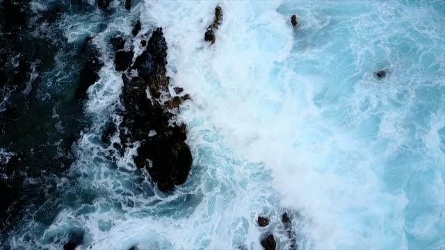 Flying Above Waves Crashing Over Rocks on Shore of Maui