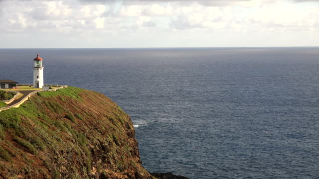 flying above white lighthouse on kauai island - butte rocky outcrop stock videos & royalty-free footage