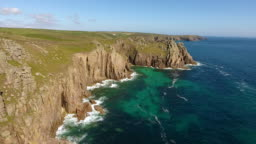 Flying along dramatic rocky rugged cliffs, turquoise sea waters, summer landscape in Cornwall, south west England.
