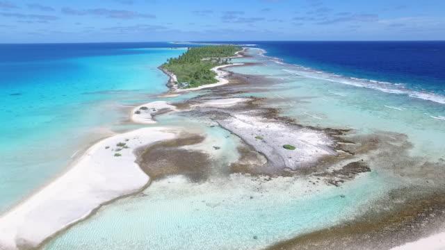 Flying along Tahanea Atoll with small hut below