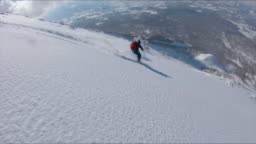 AERIAL: Flying along the male tourist skiing downhill in the scenic backcountry.